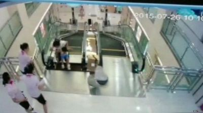 Woman killed after falling into escalator